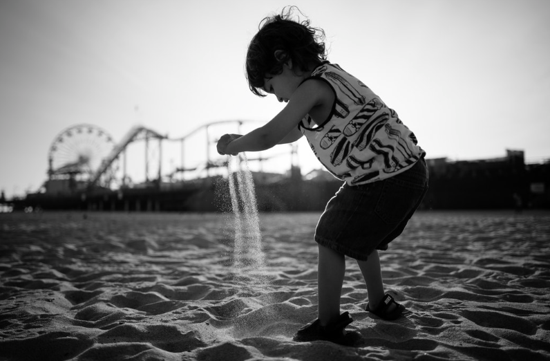 infant playing in front of santa monica pier